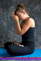 profile of woman praying on mat with mala beads