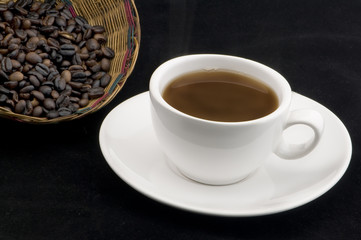 Taza de Café aislado en fondo  negro con frijoles