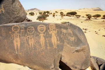 Ancient rock art in Sahara depicting four figures