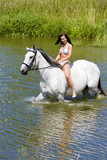 equestrian on horseback riding through water
