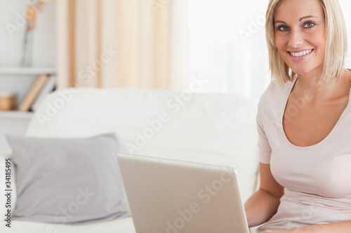 Close up of a blonde woman using a laptop