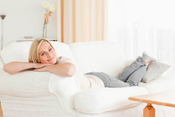 Relaxed woman lying on her sofa