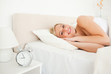 Woman waking up and an alarm clock