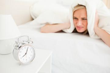 Displeased cute woman waking up