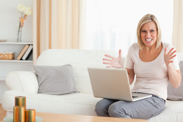 Angry blonde woman using a laptop