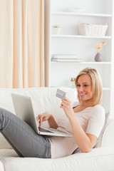 Portrait of a woman buying online whilie lying on a couch