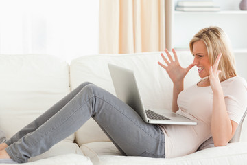 Unhappy blonde woman having trouble with her laptop