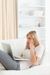 Portrait of an amazed woman having trouble her laptop