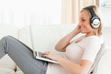 Blonde woman watching a movie with her laptop