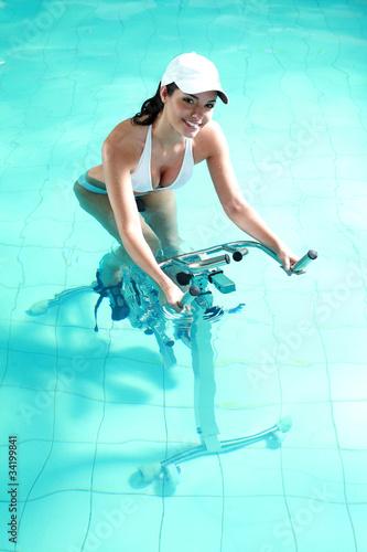 Jeune femme souriante faisant de l'aquabike