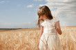 girl wearing first communion dress between barley