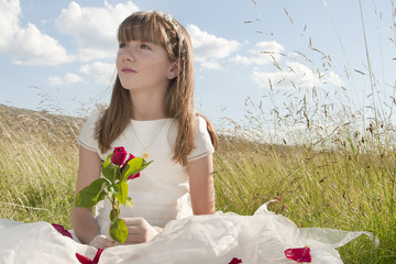 girl wearing first communion dress in the meadow