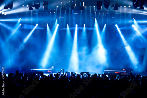 concert crowd in front of bright blue stage lights