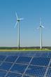 Windkrafträder und Solarmodule vor einem Rapsfeld