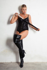 beautiful woman on high heels holding a whip