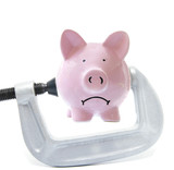 Sad piggy bank being squeezed in a vice