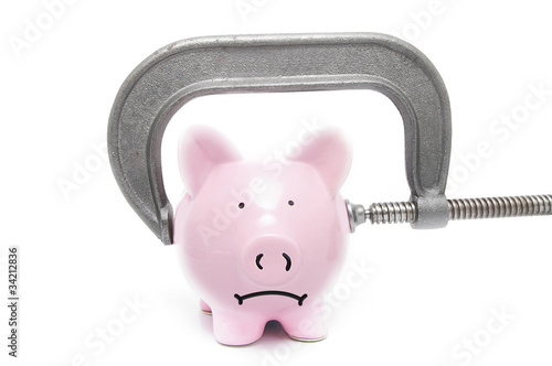 sad piggy bank being squeezed in a vice, on white
