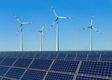 Windkrafträder und Solarmodule vor blauem Himmel