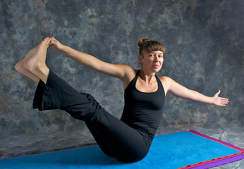 smiling young woman doing yoga posture Navasana or The Boat Pose