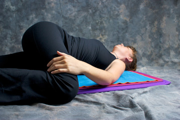 young woman doing yoga posture Ardha Jathara Parivarttanasana or