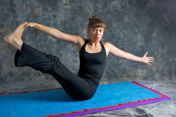 young woman doing yoga posture Navasana or The Boat Pose