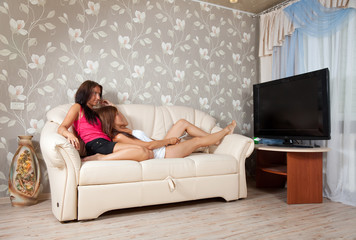 women lying  with TV Remote control