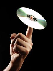 Sosteniendo un cd con un dedo.