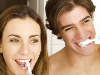 Pareja cepillando los dientes.