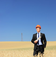 Young foreman holding blueprints in a wheat field