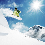 Snowboarder at jump inhigh mountains