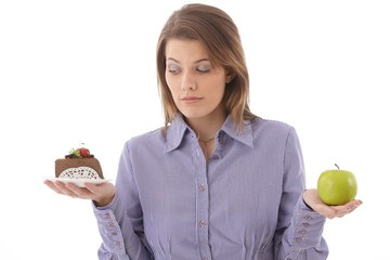Woman debating cake or apple