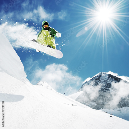 Foto op Canvas Wintersporten Snowboarder at jump inhigh mountains