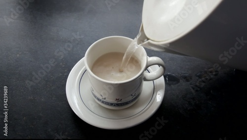 Teacup being filled with boiling water.