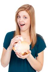 begeisterte junge frau wirft geld ins sparschwein