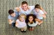 fröhliche gruppe junger menschen zeigt daumen hoch