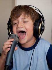 bambino che canta con microfono e cuffie