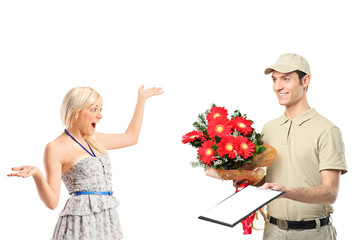Delivery boy delivering a bunch of flowers and surprised woman