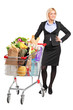Young woman posing next to a shopping cart full with groceries