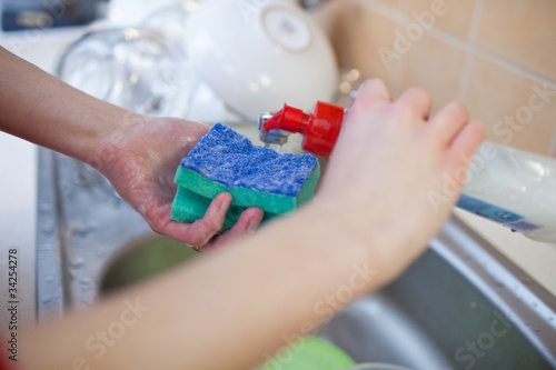 Washing of the dishes - woman hands rinsing dishes