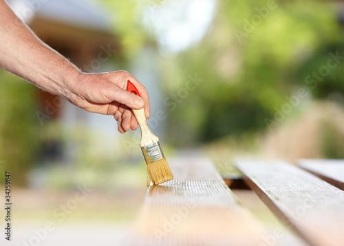 Mann streicht Brett mit Pinsel