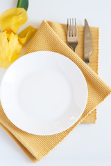 Fork, knife, plate and yellow iris flower