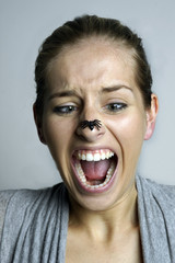 Erschrockene Frau hat eine Spinne auf der Nase