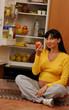 Embarazada alimentándose en una cocina.