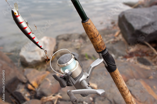 Fishing rod with reel and minnow in the beach