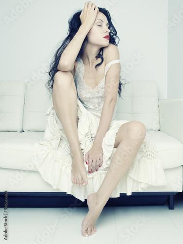 Leinwandbild Motiv Beautiful woman sitting on a sofa