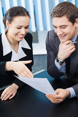 Two young happy smiling businesspeople working at office