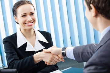 Two businesspeople or businesswoman and client handshaking