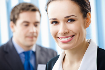 Smiling young businesswoman and colleague, at office