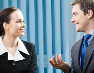 Businesspeople, or businessman and client, working at office