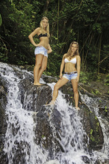 two teenage sisters standing in a waterfall in hawaii